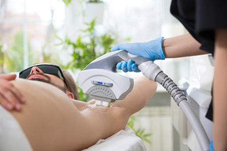 77017591 - men lying at beautician's during laser armpit hair removal therapy